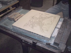 A limestone plate with a negative map of Moosburg in Bavaria is prepared for a lithography print.