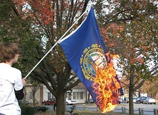 A protester burning a New Hampshire state flag.