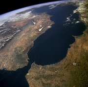 A satellite image showing the Mediterranean Sea. The Strait of Gibraltar can be seen in the bottom left (north-west) quarter of the image; to its left is the Iberian Peninsula in Europe, and to its right, the Maghreb in Africa.