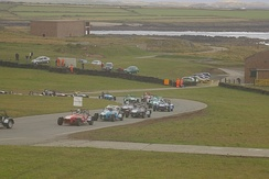 Caterhams race in 2006, with the Irish Sea in the background.