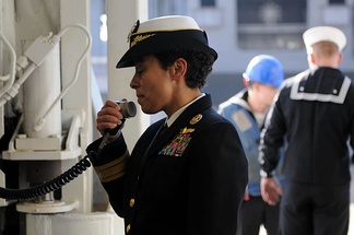 An officer uses a ship's PA system