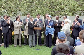 Howser (to left of podium) presents President Ronald Reagan with a Royals jacket, hat, and bat at the White House after their World Series victory.