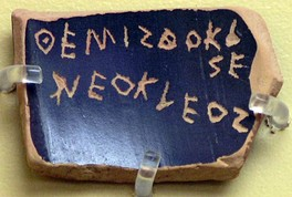 A ballot voting against Themistocles, son of Neocles, under the Athenian Democracy (see ostracism).  Inscription: ΘΕΜΙΣΘΟΚΛΕΣ ΝΕΟΚΛΕΟΣ (classical standard Θεμιστοκλῆς Νεοκλέους Themistoklês Neokléous).  The text is an example of the epichoric alphabet; note that the last two letters of Themistocles are written in a boustrophedon manner and that Ε and Ο are used for both long and short e and o.