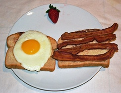 Bacon and egg on toast, garnished with a strawberry