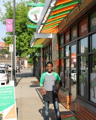 Young woman smiling outside restaurant with orange and green striped awning