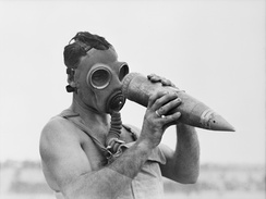 An Australian observer who has moved into a gas-affected target area to record results, examines an un-exploded shell.