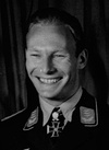 A smiling man wearing a military uniform, and an Iron Cross displayed at the front of his uniform collar.