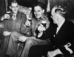 Lieutenant D. M. N. Davidson (right) of the RNVR enjoying beer with members of Z Special Unit in Brisbane after the completion of Operation Jaywick