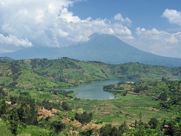 Photograph of a lake with one of the Virunga mountains behind, partially in cloud
