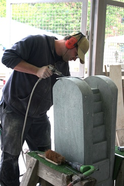 Stonemason dressing stone on a fountain with pneumatic tools