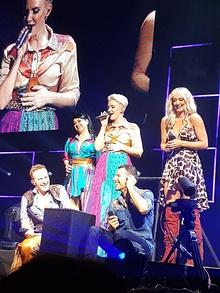 A group of five people - three women (pictured standing) and two men (pictured crouching) - standing on a stage performing a music act.