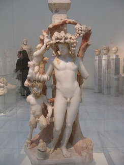 Marble table support adorned by a group including Dionysos, Pan and a Satyr; Dionysos holds a rhyton (drinking vessel) in the shape of a panther; traces of red and yellow colour are preserved on the hair of the figures and the branches; from an Asia Minor workshop, 170–180 AD, National Archaeological Museum, Athens, Greece