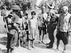 Black and white photo of three men wearing military uniforms and carrying guns with three elderly men and a teenager wearing civilian clothes