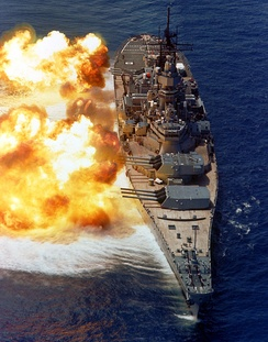 The firepower of a battleship demonstrated by USS Iowa (c. 1984). The muzzle blasts distort the ocean surface.