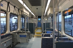 Inside an empty train with large windows, several seats arranged parallel and perpendicularly, metal handlebars, and black hand-holds. The far section of the train with additional seating is lifted up and has a short stairway.
