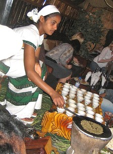 An Ethiopian woman preparing Ethiopian coffee at a traditional ceremony. She roasts, crushes and brews the coffee on the spot.