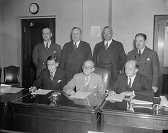 Federal Communications Commission seen in Washington, D.C., in 1937. Seated (l-r) Eugene Octave Sykes, Frank R. McNinch, Chairman Paul Atlee Walker, Standing (l-r) T.A.M. Craven, Thad H. Brown, Norman S. Case, and George Henry Payne.