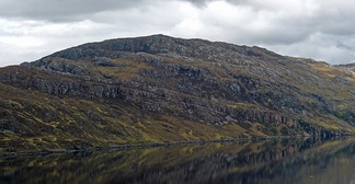 The Glencoul Thrust at Aird da Loch, Assynt in Scotland. The irregular grey mass of rock is formed of Archaean or Paleoproterozoic Lewisian gneisses thrust over well-bedded Cambrian quartzite, along the top of the younger unit.