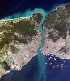 Satellite image showing a thin piece of land, densely populated on the south, bisected by a waterway