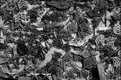 Various Marine and Navy rank insignia (as well as other devices) left at the summit of Mount Suribachi on Iwo Jima.