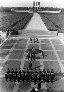 The Totenehrung (honoring of the dead) at the 1934 Nuremberg Rally. SS leader Heinrich Himmler, Adolf Hitler and SA leader Viktor Lutze (from L to R) on the stone terrace in front of the Ehrenhalle (Hall of Honor) in the Luitpoldarena. In the background is the crescent-shaped Ehrentribüne (the Tribune of Honor).