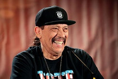 Danny Trejo wearing a snapback with long hair