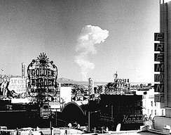 This view of downtown Las Vegas shows a mushroom cloud in the background. Scenes such as this were typical during the 1950s. From 1951 to 1962 the government conducted 100 atmospheric tests at the nearby Nevada Test Site.
