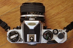Nikon FE top plate showing the film-speed and exposure compensation dials on the left, and shutter speed dial on the right.