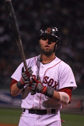 "A man in a white baseball uniform with ""RED SOX"" across the chest and a dark helmet holds a baseball bat."
