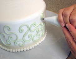 Cake decoration – buttercream swirls being piped onto the sides of this cake with a pastry bag