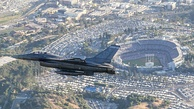 A F-16 Fighting Falcon flies past Dodger Stadium during the pre-game ceremonial flyover before Game 2.