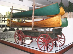 In the Adirondacks at portages that were heavily used, horse-drawn wagons like this one were furnished with racks for carrying several boats at once, for a fee. This example is typical of those used in the 1890s. (Adirondack Museum).