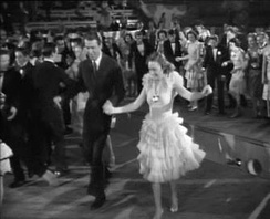 George and Mary dancing near the opening in the floor in the high school gym
