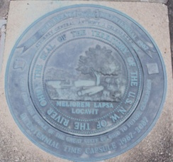"Seal of the Northwest Territory over a time capsule outside the Campus Martius Museum. The Latin phrase, ""He has planted one better than the one fallen,"" signifies the replacement of wilderness by civilization.[25]"