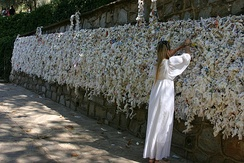The Meryemana or wishing wall at the House of the Virgin Mary in Ephesus, Turkey. Pilgrims' most frequent wishes include those for good health, peace and happiness.[415] This devotional site is one of many that is sacred to both Christians and Muslims.[416]