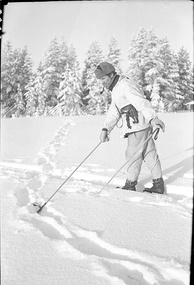 A Finnish soldier on skis, with a fur hat and a tobacco pipe in his mouth, points with a ski pole at the snowy ground where Soviet soldiers have left tracks. The Finnish troops are in pursuit.