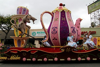 The Cat's Away, Sierra Madre Rose Float Association's float from the 2017 Rose Parade.  The teapot is decorated with pink and purple carnations and yellow strawflower embellishments, and the chassis is covered in red roses.