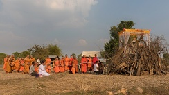 Buddhist monks procession in front of a pyre in Laos
