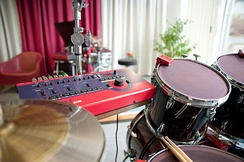 "Triggers sensors in use, here they are red and mounted on the rims of the snare drum, bass drum and hanging toms. The larger box in the same colour red is the ""brain"" to which they are connected."