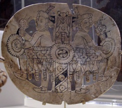 Engraved shell gorget from Spiro Mounds. The striped-center-pole, or axis mundi, divides the image in half. The cross and circle motifs also have symbolic meanings.