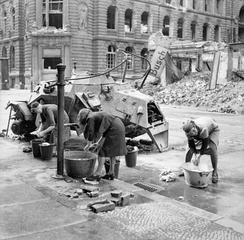 German women washing clothes at a water hydrant in a Berlin street. A knocked-out German scout car stands beside them, 3 July 1945.