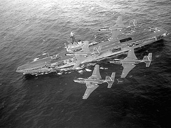 Four F2H-3 Banshee fly overhead HMCS Bonaventure. Bonaventure was the last aircraft carrier in service with the Royal Canadian Navy.