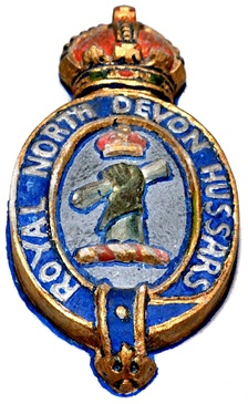 Badge of Royal North Devon Hussars, as seen on framed mural monument in Exford Church, Somerset, to Major Morland Greig (1864–1915), of Edgcott, Exford, Master of the Devon and Somerset Staghounds, killed in action at Gallipoli. The badge is derived from the crest of John Rolle, 1st Baron Rolle (d.1842),[a] of Stevenstone, who played a significant role in raising the predecessor regiment: A cubit arm erect vested or charged with a fess indented double cotised azure in the hand a roll of parchment. The badge is also shown, but with the hand grasping a palm frond, sculpted on the mural monument in the Church of St Giles in the Wood, Devon, to Captain John Oliver Clemson (1882-1915) of Stevenstone, also killed fighting with the same regiment at Gallipoli