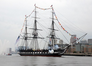 USS Constitution, dressed overall, fires a seventeen-gun salute in Boston Harbor, 4 July 2014.