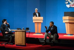 President Obama talks with Ron Klain during presidential debate preparations. Senator John Kerry, at podium, played the role of Mitt Romney during the preparatory sessions.