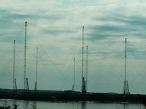 The trideco antenna array at the US Navy's Cutler VLF transmitter at Cutler, Maine, which transmits tactical orders to submerged submarines at a frequency of 24 kHz and a power of 1.8 megawatts, one of the most powerful transmitters in the world.  It consists of two identical trideco antennas, each consisting of 13 towers supporting a 6 pointed wire topload about a mile across.  The picture (left) shows a few of the towers, (right) the central mast and 6 vertical radiators connection to the panels, showing the long 50 ft. insulator strings and corona rings required to withstand the 200 kV voltage on the antenna.