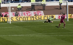 A football player scores a goal against the opposing goalkeeper from a penalty-kick. Stewards and camera-operators are visible behind the goal net.