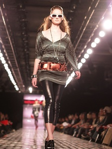 A model wearing shiny leather-look leggings on a catwalk.