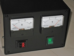 A simple general purpose desktop power supply used in electronic labs, with power output connector seen at lower-left and power input connector (not shown) located at the rear