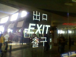 "Multilingual sign at an exit of SM Mall of Asia in Pasay City, Philippines. Three or four languages are shown: Japanese/Mandarin Chinese (""deguchi"" or ""chūkǒu"", respectively), English (""exit"") and Korean (""chulgu""). While Filipinos themselves are anglophone, such signs cater to the growing number of Koreans and other foreigners in the country."